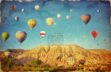 Grunge image  of colorful hot air balloons against blue sky