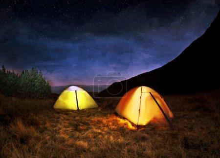 Illuminated yellow camping tent under stars at night