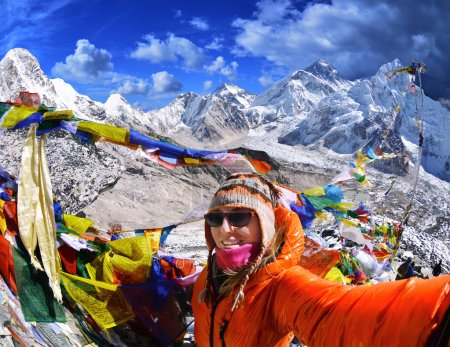 Smiling young woman takes a selfie  on mountain peak  Kala Patthar in Nepal