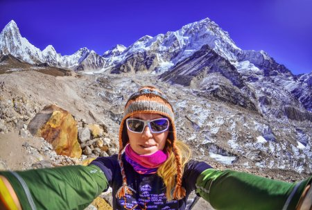 Smiling young woman takes a selfie  on mountain peak ,Everest region, Nepal