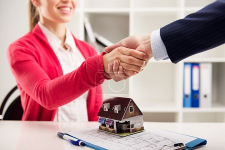 Photo for Two business people shaking hands as successful agreement in real estate agency office. Concept of housing purchase and insurance. - Royalty Free Image