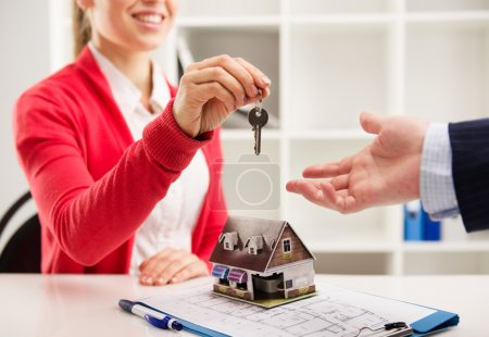 Photo for Closeup of smiling woman realtor giving key of new apartment to client. Female house agent sitting at the desk with house miniature and plan. - Royalty Free Image