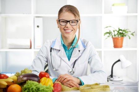 Photo pour Femme diététiste souriante assise à la table avec des fruits et légumes colorés à la clinique. Concept de régime, perdre du poids et soins de santé . - image libre de droit
