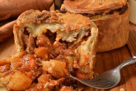 Photo pour Pâtisserie remplie de morceaux de boeuf tendre, pommes de terre, champignons, carottes, herbes et sauce à l'ale - image libre de droit