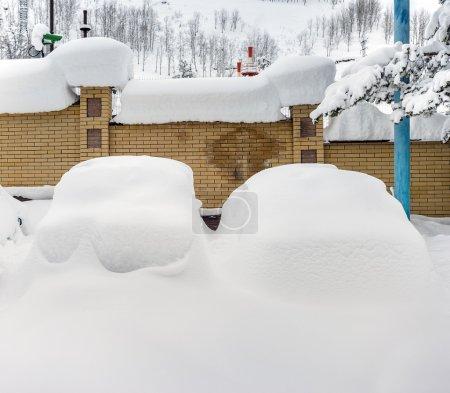 Photo pour Voitures couvertes de neige dans le parking en zone rurale de montagne - image libre de droit