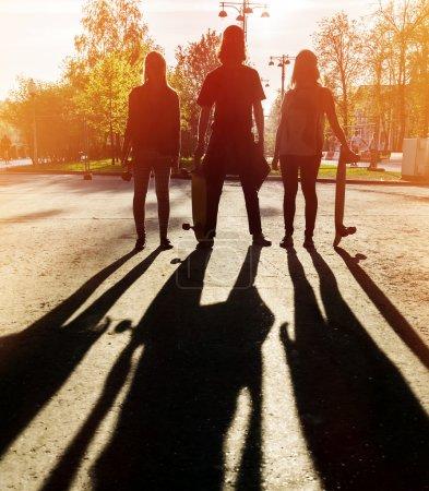 Silhouette three friends skateboarders in city