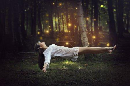 Photo pour Lévitation des femmes dans la forêt entourée de fées. Fantasme et surréalisme - image libre de droit