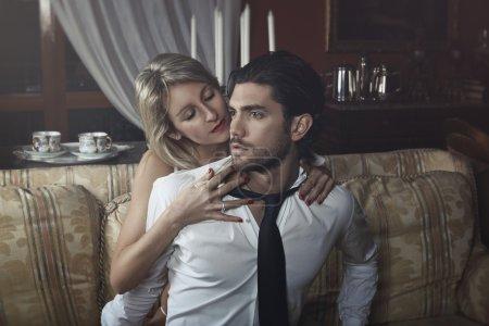 Seductive woman undressing handsome man