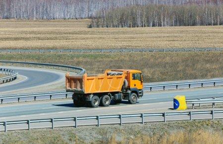 Photo pour Grosse camion à benne jaune sur la route du pays - image libre de droit