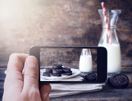 Man photographing cookies and bottle of milk
