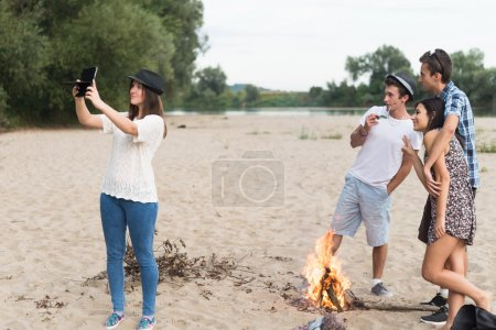 Young Adults Taking Pictures And Selfies On Sandy Beach