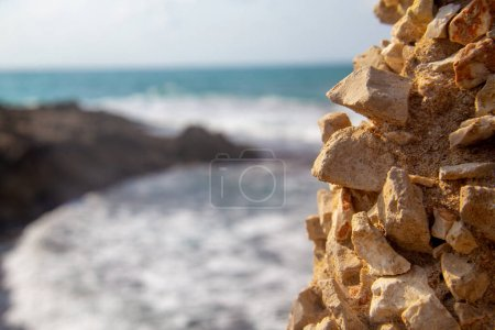 Photo for Seascape - a large shell rock in the foreground and light waves and quiet skies in the background (bokeh). - Royalty Free Image