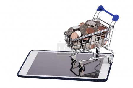 Shopping basket full of US coins on a tablet pc isolated on a white background