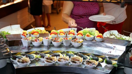 Photo pour Femme prend des fruits de mer de la table de buffet. - image libre de droit