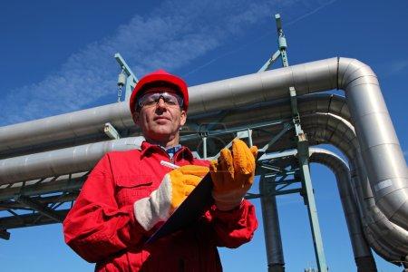 Photo pour Travailleur portant des salopettes rouges et un casque de sécurité, écrivant sur le presse-papiers à côté des pipelines . - image libre de droit