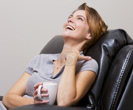 Photo pour Femme caucasienne assise dans le salon à boire du café - image libre de droit