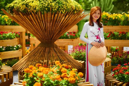 Photo for Culture Of Asia. Beautiful Happy Smiling Young Asian Woman Wearing Traditional White Ao Dai Dress ( Clothing ), Vietnamese Conical Hat ( Non La ) Leaf Hat In Flower Garden In Ho Chi Minh City, Vietnam - Royalty Free Image