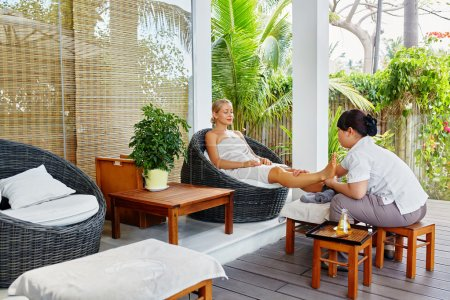 Photo for Spa Foot Therapy. Woman Body Care Treatment. Masseur Massaging Young Female Feet With Aromatherapy Oil Outside In Spa Salon Garden. Relaxing Recreational Massage. Skin Care, Beauty Procedure Concept - Royalty Free Image