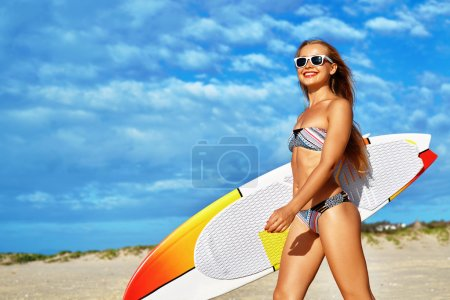 Photo for Healthy Active Lifestyle. Surfing. Water Sports. Beautiful Athletic Surfer Woman With Sexy Fit Body In Bikini With Surf Board Walking On Sea Beach. Summer Vacation. Extreme Sport. Summertime Fun Hobby - Royalty Free Image