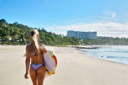 Photo pour Mode de vie sain et actif. Surfer. Sports nautiques. Belle femme surfeuse athlétique avec un corps sexy en bikini avec planche de surf marchant sur la plage de la mer. Vacances d'été. Sport extrême. Plaisir d'été Hobby - image libre de droit