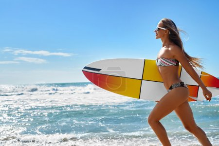 Photo for Extreme Water Sport. Surfing. Healthy Athletic Young Surfer Girl With Sexy Fit Body In Bikini Holding Surf Board, Running On Sea Beach. Summer Vacation. Lifestyle. Leisure, Hobby, Wellness, Fitness - Royalty Free Image