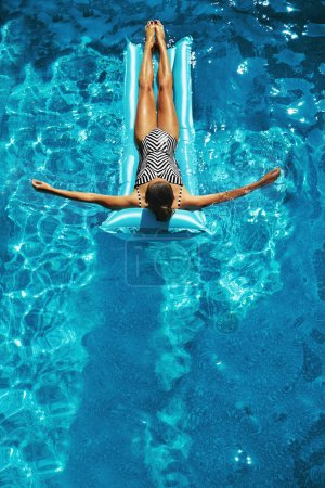 Photo for Summer Vacations. Beautiful Sexy Happy Smiling Woman With Fit Body, Healthy Skin In Swimwear Sunbathing, Floating On Float Swim Air Mattress, Rings In Swimming Pool Water. Beauty, Wellness. Recreation - Royalty Free Image