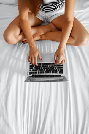 Photo for Woman Using Computer At Home. Closeup View Of Female Freelancer With Long Fit Legs Chatting, Typing On Laptop, Relaxing On Bed. Girl Working On Pc, Notebook. Online Shopping. Communication Technology. - Royalty Free Image