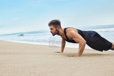 Man Exercising, Doing Push Up Exercises On Beach. Fitness Workout