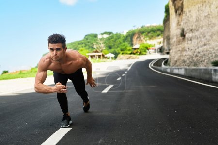Photo for Athletics. Athletic Man With Fit Muscular Body In Starting Position For Running On Road. Handsome Runner Ready To Start Sprint Race. Fitness Model Training Outdoors In Summer. Sports Workout Concept - Royalty Free Image