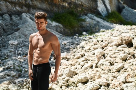 Photo for Active Hot Fitness Male Model Resting After Exercising And Running Workout Outdoors. Topless Handsome Healthy Athletic Man With Muscular Body In Summer Sportswear Standing On Rocky Hill. Sport Concept - Royalty Free Image