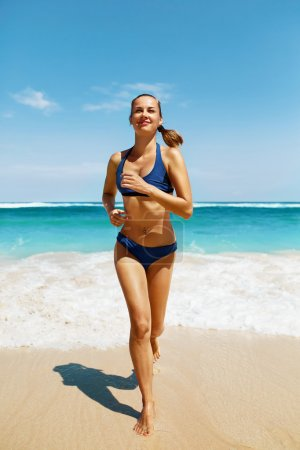 Photo for Beach Run. Fitness Woman Running On Sand. Beautiful Healthy Happy Smiling Girl With Sexy Fit Body In Sport Bikini Swimwear Having Fun On Summer Vacations Near Sea. Active Lifestyle, Recreation Concept - Royalty Free Image