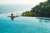 Luxury Resort. Man Relaxing In Swim Pool. Summer Travel Vacation