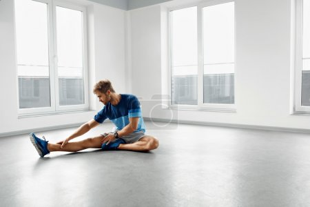 Stretch Exercise. Handsome Healthy Man Stretching Before Workout
