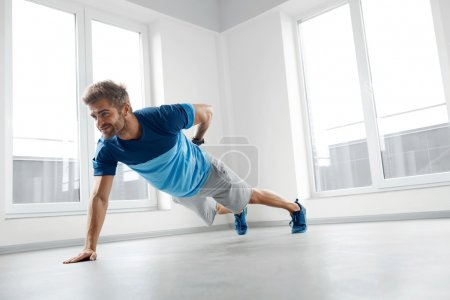 Man Workout Exercises. Fitness Male Model Doing Push Ups Indoors