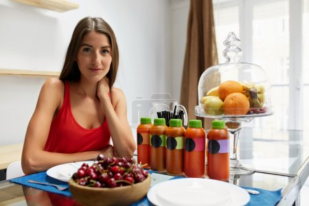 Photo for Healthy Diet Food. Detox Juice, Fresh Smoothie Bottles Standing On Table. Closeup Of Beautiful Smiling Woman With Fruits And Weight Loss Diet Drinks Sitting At Kitchen Table. Fitness Nutrition Concept - Royalty Free Image