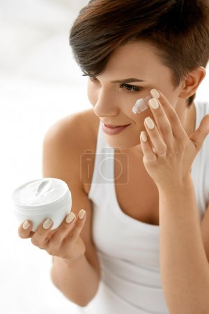 Beauty Skin Care. Beautiful Woman Applying Cosmetic Face Cream