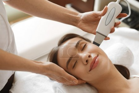 Photo for Face Skin Care. Beautiful Woman Receiving Ultrasound Cavitation Peeling In Beauty Salon. Girl Getting Ultrasonic Facial Treatment, Skin Cleansing Procedure At Cosmetology Center. High Resolution Image - Royalty Free Image