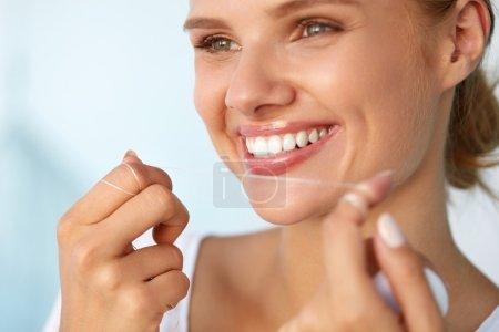 Photo pour Hygiène dentaire. Gros plan de belle femme souriante heureuse avec visage de beauté et nettoyage parfait du sourire, soie dentaire dents blanches saines en utilisant Floss. Santé buccodentaire, concept de soins dentaires. Image haute résolution - image libre de droit