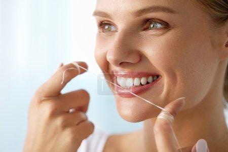 Photo pour Soins des dents. Gros plan de belle femme souriante heureuse avec un sourire parfait Nettoyage de ses dents blanches en bonne santé, soie dentaire en utilisant Floss. (Bouche) Hygiène buccale, concept de santé dentaire. Image haute résolution - image libre de droit