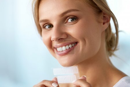 Photo pour Blanchiment des dents. Closeup Portrait de belle heureuse jeune femme souriante avec parfait sourire, des dents blanches saines tenue bande de blanchiment des dents. Beauté Soins dentaire et le Concept de santé. Image en haute résolution - image libre de droit