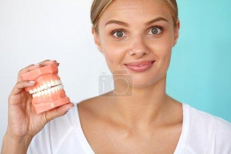 Photo pour Chirurgie. Verticale de plan rapproché de belle femme de sourire avec le sourire blanc, dents saines retenant le modèle dentaire artificiel de la mâchoire humaine. Oral, Dental Health, Tooth Care Concepts. Image haute résolution - image libre de droit