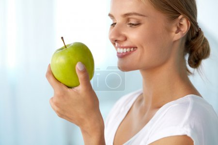 Beautiful Smiling Woman With White Teeth Eating Green Apple