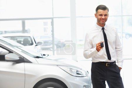 Photo pour Vendeur de voitures, donnant les clés d'une voiture neuve au Showroom - image libre de droit