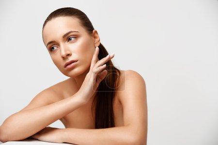Photo pour Spa belle femme toucher son visage sur fond de lumière - image libre de droit
