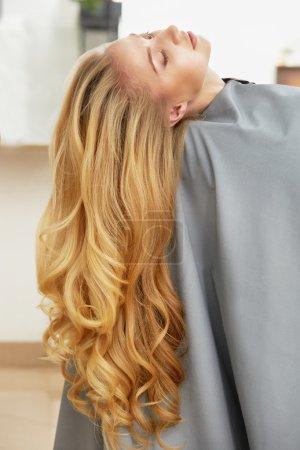 Photo pour Femme avec de longs cheveux blonds assis dans le salon de coiffure - image libre de droit