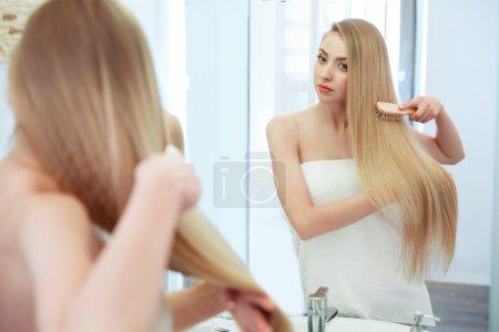 Hair. Beautiful Blond Brushing Her Hair. Hair Care. Spa Beauty M