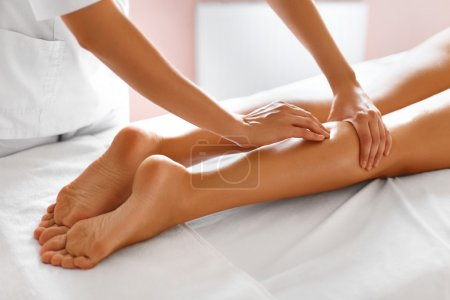 Photo for Spa Woman. Close-up Of Sexy Woman Getting Spa Treatment. Leg Massage Therapy In Spa Salon. Masseur Applying Moisturizing Oil And Massaging Beautiful Long Tanned Female Legs. Body Care, Skin Care, Wellbeing, Wellness Concept. - Royalty Free Image