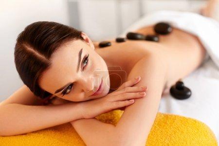 Photo pour Massage aux pierres de Spa. Jeune femme ont des traitements de Massage aux pierres chaudes. Spa pierres chaudes - image libre de droit