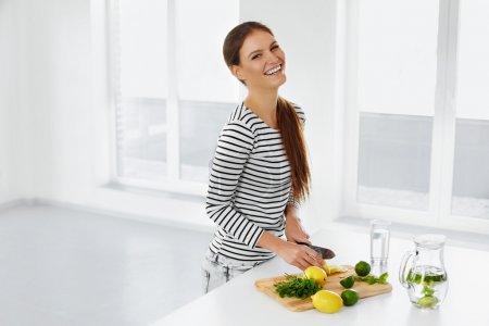 Photo pour Mode de vie sain et manger. Femme dans la cuisine coupant des agrumes, des citrons et des chaux. Vitamine C. Eau de désintoxication. De la limonade. Régime alimentaire. Concept de régime. Nourriture saine. Bien-être, Bien-être . - image libre de droit