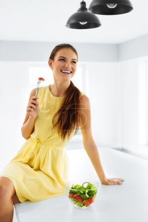 Photo for Healthy Food. Close Up Of Happy Smiling Girl Eating Vegetable Vegetarian Salad In Modern Kitchen. Healthy Eating And Lifestyle. Health, Beauty, Diet Concept. Nutrition. - Royalty Free Image